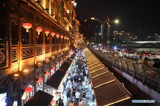 Visitors are seen in Hongyadong scenic spot at night in Yuzhong District, southwest China's Chongqing Municipality, Sept. 9, 2019. The development of nighttime economy in Chongqing enriches citizens' consumption choices and attracts visitors. Nighttime economy refers to business activities between 6 p.m. (1000 GMT) and 6 a.m. (2200 GMT) in the service sector. (Xinhua/Tang Yi)