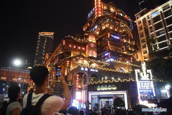 A visitor takes photos in Hongyadong scenic spot at night in Yuzhong District, southwest China's Chongqing Municipality, Sept. 9, 2019. The development of nighttime economy in Chongqing enriches citizens' consumption choices and attracts visitors. Nighttime economy refers to business activities between 6 p.m. (1000 GMT) and 6 a.m. (2200 GMT) in the service sector. (Xinhua/Tang Yi)