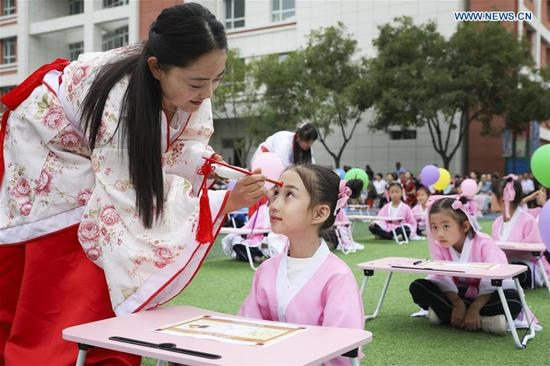 A teacher makes cinnabar moles on a child's forehead during a first writing ceremony, a traditional education activity, at a school in Lanzhou, northwest China's Gansu Province, Sept. 10, 2019. (Photo by Ma Xiping/Xinhua)