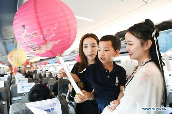 A train stewardess (1st R) in traditional Chinese costume and passengers guess lantern riddles to greet the upcoming Mid-Autumn Festival aboard a bullet train from Shanghai to Nanjing of east China's Jiangsu Province, Sept. 12, 2019. The Mid-Autumn Festival falls on Sept. 13 this year. (Xinhua/Li Bo)