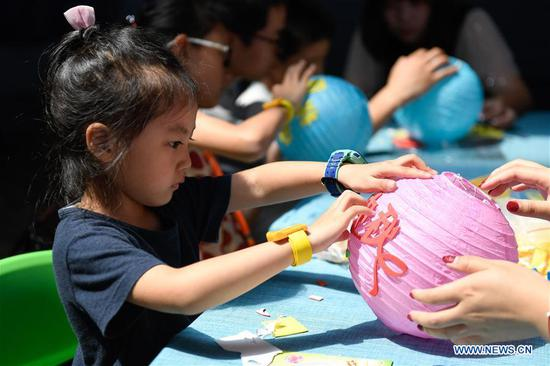 Children make lanterns at an activity to celebrate the Mid-Autumn Festival in Hangzhou, east China's Zhejiang Province, Sept. 13, 2019. Children took part in various activities including handicrafts and mooncake making to enjoy the traditional Chinese festival on Friday. (Xinhua/Huang Zongzhi)