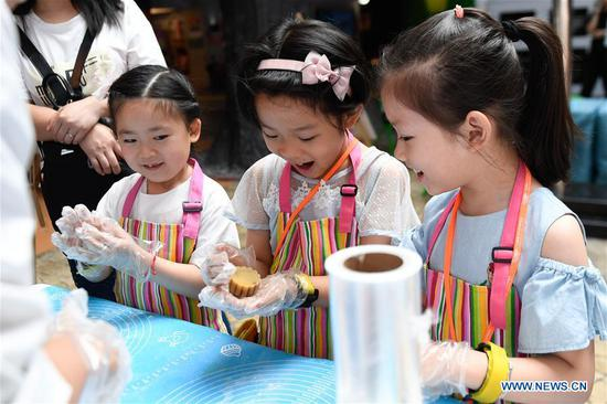 Children learn to make mooncakes at an activity to celebrate the Mid-Autumn Festival in Hangzhou, east China's Zhejiang Province, Sept. 13, 2019. Children took part in various activities including handicrafts and mooncake making to enjoy the traditional Chinese festival on Friday. (Xinhua/Huang Zongzhi)
