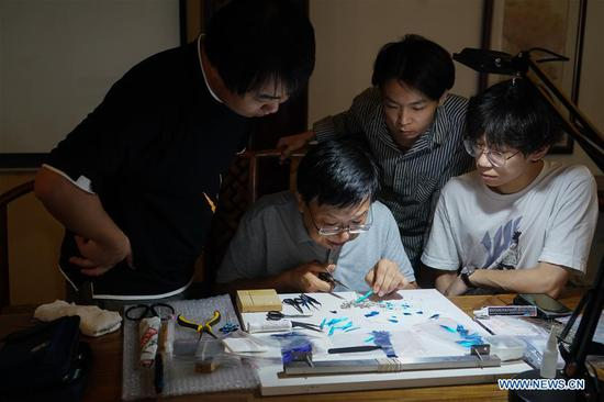 Zhao Shuxian (2nd L) instructs his apprentices Ling Jiawei (1st L), Fu Lei (2nd R) and Yan Xin to make velvet flower handicrafts at the workshop of Nanjing Intangible Cultural Heritage Exhibition Center in Nanjing, capital of east China's Jiangsu Province, Sept. 14, 2019. Zhao Shuxian, 65, a representative inheritor of the