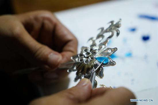 Zhao Shuxian makes a velvet flower accessory at the workshop of Nanjing Intangible Cultural Heritage Exhibition Center in Nanjing, capital of east China's Jiangsu Province, Sept. 14, 2019. Zhao Shuxian, 65, a representative inheritor of the
