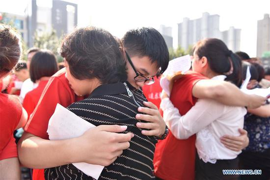 Students embrace their family members during a collective coming-of-age ceremony at the Dingzhou Middle School in Dingzhou, north China's Hebei Province, Sept. 16, 2019. (Xinhua/Zhu Xudong)