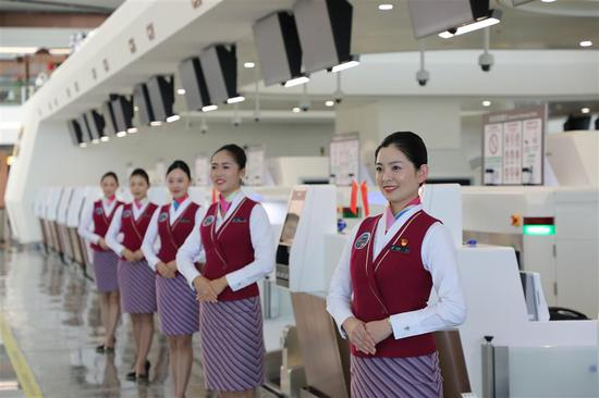 Crew members greet the first batch of passengers to the Daxing airport beside a line of self-service check-in machines.