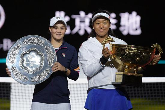 Naomi Osaka (right) of Japan poses with the winner's trophy after her 3-6, 6-3, 6-2 victory over Ashleigh Barty of Australia in the women's final of the China Open in Beijing on Sunday.