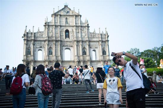 """Tourists visit the Ruins of St. Paul's in south China's Macao Special Administrative Region (SAR), on Oct 8, 2019. The visitor arrivals in Macao reached more than 980,000 during the """"Golden Week"""" of the National Day holiday, up 11.5 percent year-on-year, the SAR tourism office said on Tuesday. Visitor arrivals from the mainland reached more than 798,000 during the seven-day holiday, up by 9.4 percent year-on-year, the Macao Government Tourism Office (MGTO) said. (Xinhua/Cheong Kam Ka)"""