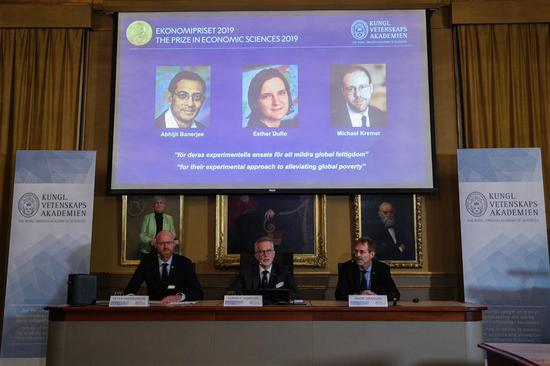 """The photos of the winners of the 2019 Nobel Prize in Economics are seen at the Royal Swedish Academy of Sciences, Stockholm, Sweden, Oct. 14, 2019. The 2019 Nobel Prize in Economics has been awarded to Abhijit Banerjee, Esther Duflo and Michael Kremer """"for their experimental approach to alleviating global poverty,"""" the Royal Swedish Academy of Sciences announced Monday. (Xinhua/Zheng Huansong)"""