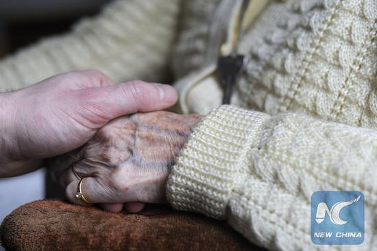 This file photo taken on March 18, 2011 shows a woman, suffering from Alzheimer's desease, holding the hand of a relative in a retirement house in Angervilliers, eastern France. (Xinhua/AFP PHOTO)