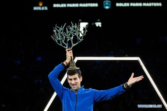 Novak Djokovic of Serbia poses with the trophy after the final match against Denis Shapovalov of Canada at the Rolex Paris Masters 1000 held at the AccorHotels Arena in Paris, France, Nov. 3, 2019. (Photo by Aurelien Morissard/Xinhua)