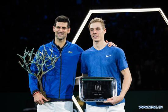 Novak Djokovic (L) of Serbia and Denis Shapovalov of Canada pose during the awarding ceremony after the final match at the Rolex Paris Masters 1000 held at the AccorHotels Arena in Paris, France, Nov. 3, 2019. (Photo by Aurelien Morissard/Xinhua)