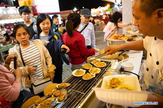 Visitors select food in the 19th Macao Food Festival at Sai Van Lake Square in Macao, south China, Nov. 8, 2019. The 19th Macao Food Festival kicked off in Macao on Friday with about 160 food stalls to serve the visitors. (Xinhua/Cheong Kam Ka)