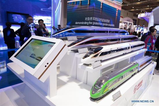 Visitors look at model trains at the China pavilion during the second China International Import Expo (CIIE) in Shanghai, east China, Nov. 8, 2019. The China pavilion showcases achievements China has made over the past 70 years, as well as its culture and landscape. (Xinhua/Jin Liwang)