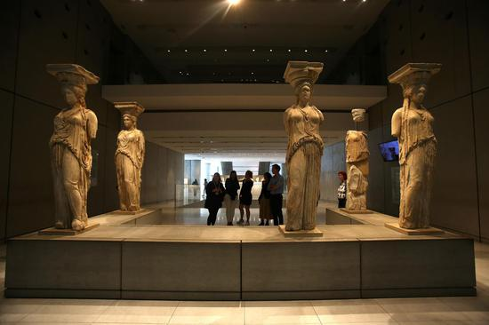 Visitors look at Caryatids of the Erechtheion at the Acropolis Museum in Athens, Greece, Nov. 7, 2019. (Xinhua/Marios Lolos)