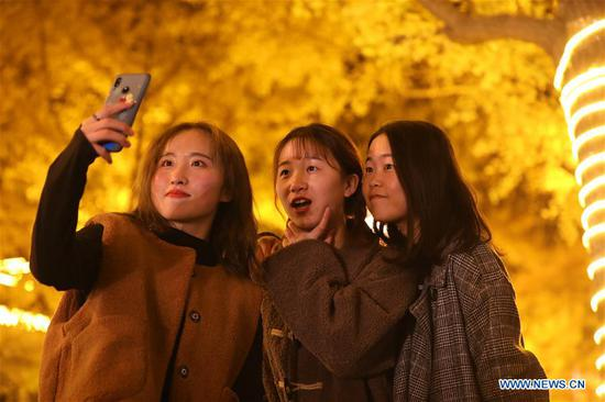 Girls take a selfie in an alley of gingko trees in Tianshui City, northwest China's Gansu Province, Nov. 14, 2019. (Xinhua/Guo Gang)