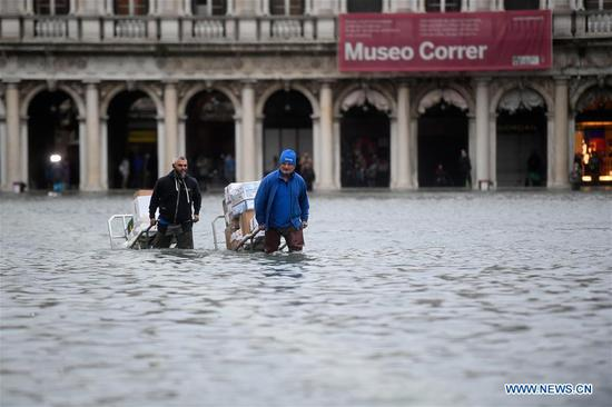 People wade through the flood in Venice, Italy, Nov. 15, 2019. The Italian government declared a state of emergency in Venice, after the ancient lagoon city was severely flooded earlier this week, Prime Minister Giuseppe Conte said on Thursday. At least two people died and severe damages were registered in Italy's lagoon city of Venice, following the highest water tide since 1960s, local authorities said on Wednesday. (Photo by Alberto Lingria/Xinhua)
