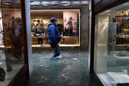 A man wades through the flood in Venice, Italy, Nov. 15, 2019. The Italian government declared a state of emergency in Venice, after the ancient lagoon city was severely flooded earlier this week, Prime Minister Giuseppe Conte said on Thursday. At least two people died and severe damages were registered in Italy's lagoon city of Venice, following the highest water tide since 1960s, local authorities said on Wednesday. (Photo by Alberto Lingria/Xinhua)