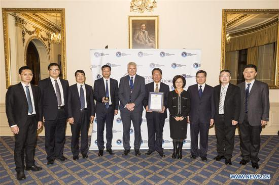 Members of China's Chang'e-4 mission team pose for a group photo with guests at the award ceremony of Royal Aeronautical Society (RAeS) in London, Britain, on Nov. 25, 2019. China's Chang'e-4 mission team on Monday received the only Team Gold Medal of the year awarded by Royal Aeronautical Society (RAeS) of the United Kingdom at its annual award ceremony held in London. (Photo by Ray Tang/Xinhua)