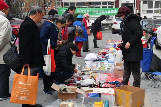 Residents exchange the points accumulated by garbage sorting for gifts in Guangming community in Beijing on November 23, 2019.