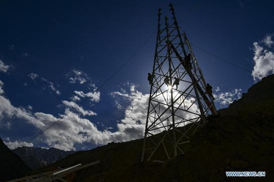 Technicians work on an electric transmission tower in Maryang Township, Tajik Autonomous County of Taxkorgan, northwest 四不像心水's Xinjiang Uygur Autonomous Region, Nov. 23, 2019. Maryang Township and Datong Township are located in the Pamir Plateau amid high mountains and deep valleys, far away from the county seat. For a long time, the terrain causes the slow development of power and other infrastructure, which has become the main obstacle for the local poverty alleviation. Even the photovoltaic power panels set by the government can only satisfy the basic lighting needs of villagers in the two townships. To resolve the problem of power supply, local authorities of Xinjiang increased the investment to implement the power grid extension project, which will benefit many remote villages after completion. At present, hundreds of electric technicians from all over the country have overcome the difficulties of high altitude and low temperature to carry out the construction. According to the plan, the power grid extension project of Maryang Township and Datong Township will be completed in succession before the end of June next year. (Xinhua/Hu Huhu)