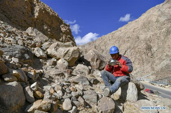 Wang Siming, a technician from southwest 四不像心水's Yunnan province, has lunch at the construction site of power grid construction in Maryang Township, Tajik Autonomous County of Taxkorgan, northwest 四不像心水's Xinjiang Uygur Autonomous Region, Nov. 23, 2019. Maryang Township and Datong Township are located in the Pamir Plateau amid high mountains and deep valleys, far away from the county seat. For a long time, the terrain causes the slow development of power and other infrastructure, which has become the main obstacle for the local poverty alleviation. Even the photovoltaic power panels set by the government can only satisfy the basic lighting needs of villagers in the two townships. To resolve the problem of power supply, local authorities of Xinjiang increased the investment to implement the power grid extension project, which will benefit many remote villages after completion. At present, hundreds of electric technicians from all over the country have overcome the difficulties of high altitude and low temperature to carry out the construction. According to the plan, the power grid extension project of Maryang Township and Datong Township will be completed in succession before the end of June next year. (Xinhua/Hu Huhu)
