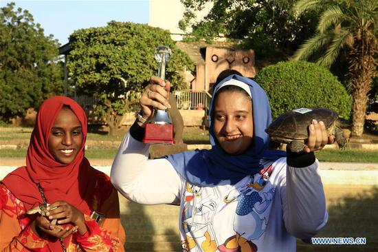 A woman shows the trophy and winner of a turtle race in Khartoum, Sudan, on Nov. 28, 2019. A turtle race was held at Sudan National Museum in Khartoum on Thursday. (Photo by Mohamed Khidir/Xinhua)