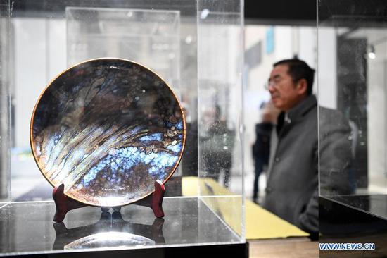 A visitor walks by a ceramic artwork at the Belt and Road Ceramic Expo Center in Rongchang District of southwest China's Chongqing Municipality, Dec. 1, 2019. The Belt and Road Ceramic Expo