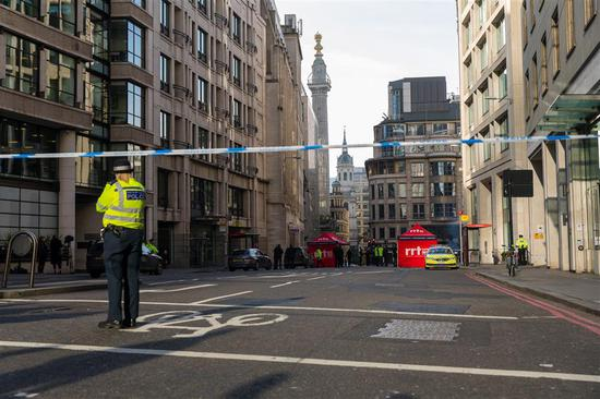 A police officer stands behind a cordon near the crime scene at London Bridge in London, Britain, on Saturday.