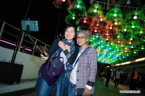 Visitors take a selfie during the 2019 Macao Light Festival in south China's Macao, Dec. 1, 2019. (Xinhua/Cheong Kam Ka)