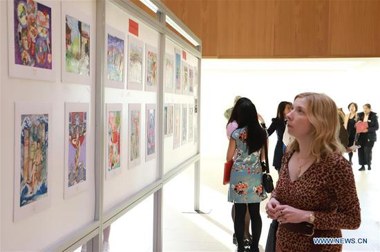 "A woman views an exhibition of paintings at the award ceremony of ""China in My Eyes Art Competition"" in Dublin, Ireland, Dec. 1, 2019. An award ceremony of a painting competition aiming to promote a better understanding of China among Irish primary and secondary school students was held here on Sunday. Named ""China in My Eyes Art Competition"", the event is co-organized by Confucius Institutes of University College Dublin (UCD) and University College Cork (UCC) with the support from the Chinese embassy in Ireland. (Xinhua)"