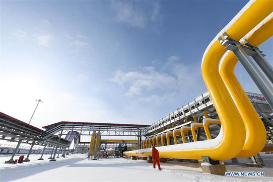 A staff member walks past pipelines in the gas-distributing and compressing station of the China-Russia east-route natural gas pipeline in the city of Heihe, the first stop after the Russia-supplied natural gas enters China, northeast China's Heilongjiang Province, Nov. 19, 2019. The China-Russia east-route natural gas pipeline was put into operation on Monday. The pipeline is scheduled to provide China with 5 billion cubic meters of Russian gas in 2020 and the amount is expected to increase to 38 billion cubic meters annually from 2024, under a 30-year contract worth 400 billion U.S. dollars signed between the China National Petroleum Corp (CNPC) and Russian gas giant Gazprom in May 2014. The cross-border gas pipeline has a 3,000-km section in Russia and a 5,111-km stretch in China. (Xinhua/Wang Jianwei)