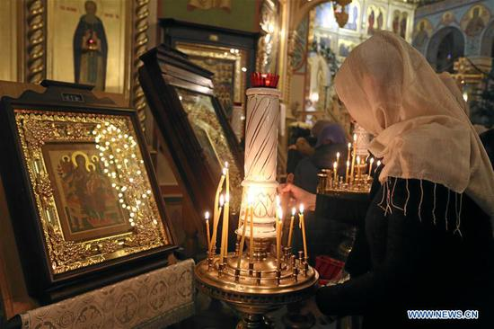 A woman lights a candle during a Christmas service at Riga Nativity of Christ Orthodox Cathedral in Riga, Latvia, on Jan. 6, 2020. Orthodox Christians celebrate Christmas on Jan. 7 according to the Julian calendar. (Photo by Edijs Palens/Xinhua)
