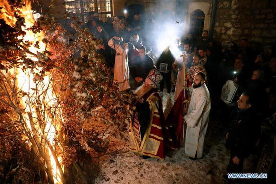 Bosnian Orthodox Priest burns dried oak branches during a traditional ceremony in front of the Old Orthodox Church in Sarajevo, Bosnia and Herzegovina, on Jan. 6, 2020. Orthodox Christians celebrate Christmas on Jan. 7 according to the Julian calendar. (Photo by Nedim Grabovica/Xinhua)