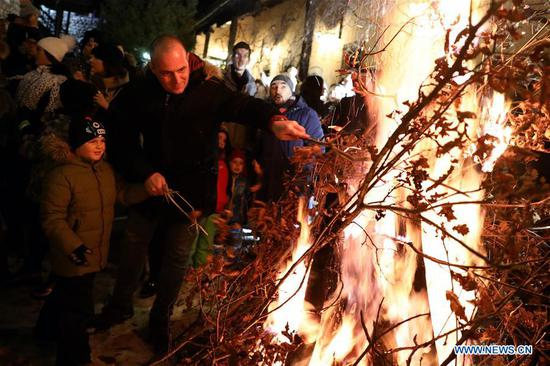 People burn dried oak branches during a traditional ceremony in front of the Old Orthodox Church in Sarajevo, Bosnia and Herzegovina, on Jan. 6, 2020. Orthodox Christians celebrate Christmas on Jan. 7 according to the Julian calendar. (Photo by Nedim Grabovica/Xinhua)