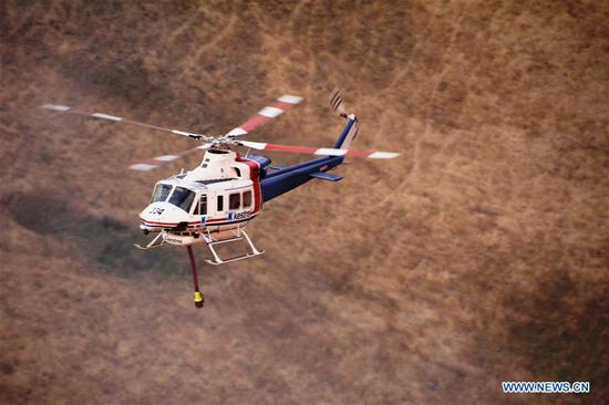 Photo taken on Dec. 20, 2019 shows a helicopter working at Lexton bush fire site in western Victoria, Australia. The Australian government launched the National Bushfire Recovery Agency which would be funded with an initial two billion Australian dollars (1.38 billion U.S. dollars) on Monday. (Wayne Riggs/CFA/Handout via Xinhua)