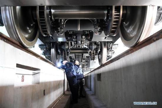 Railway workers conduct maintenance checks on a CR200J bullet train at a workshop in southwest China's Chongqing Municipality, Jan. 7, 2020. The Chongqing section of China Railway Chengdu Group Co., Ltd recently organized maintenance checks on CR200J trains, a new member of China's Fuxing bullet trains, to prepare for the upcoming Spring Festival travel rush. (Xinhua/Tang Yi)