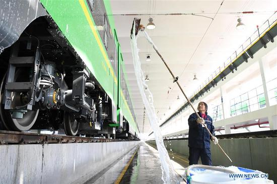 A railway worker cleans a CR200J bullet train at a workshop in southwest China's Chongqing Municipality, Jan. 7, 2020. The Chongqing section of China Railway Chengdu Group Co., Ltd recently organized maintenance checks on CR200J trains, a new member of China's Fuxing bullet trains, to prepare for the upcoming Spring Festival travel rush. (Xinhua/Tang Yi)