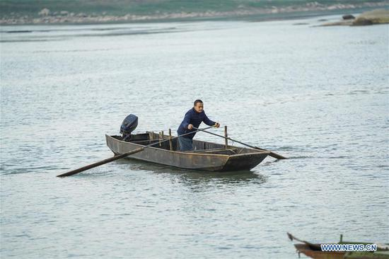 Zhao Zelun rows his boat offshore Zhongba Island in Chongqing, southwest China, Jan. 7, 2020. From Jan. 1, 2020, China began a 10-year fishing ban in key areas of the Yangtze River to protect biodiversity. Zhao, finishing his 30 years' career as fisherman, started a farm hostel business in Zhongba Island. (Xinhua/Liu Chan)