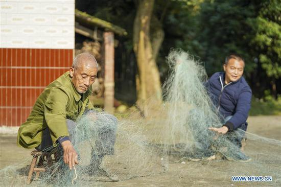 Zhao Zelun and his father sort old fishing net in Zhongba Island in Chongqing, southwest China, Jan. 7, 2020. From Jan. 1, 2020, China began a 10-year fishing ban in key areas of the Yangtze River to protect biodiversity. Zhao, finishing his 30 years' career as fisherman, started a farm hostel business in Zhongba Island. (Xinhua/Liu Chan)
