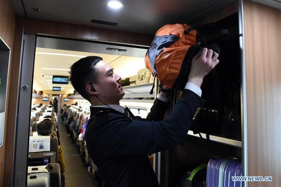 Train crew member Liu Hengduo arranges the luggage on the train G24 from Hefei of east China's Anhui Province to Beijing, Jan. 12, 2020. A group of young train crew employees from the Hefei section of China Railway Shanghai Group Co., Ltd. made their debut during the Spring Festival travel rush recently. Five out of six members from this team were born in 2000. On Jan. 12, the post-2000s team started their work during the country's largest annual migration on the train G24 from Hefei to Beijing. (Photo by Zhou Mu/Xinhua)