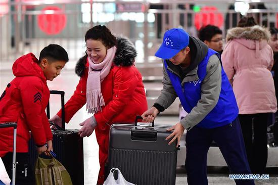 A volunteer helps passengers with their luggage at Lanzhou Railway Station in Lanzhou, capital of northwest China's Gansu Province, Jan. 13, 2020. During the Spring Festival travel rush, Lanzhou Railway Station and Lanzhou West Railway Station roll out a special voluntary service named