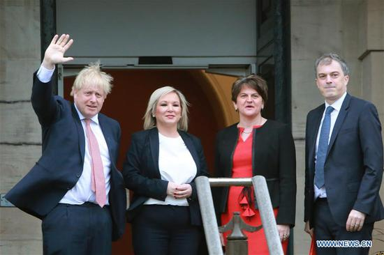 "British Prime Minister Boris Johnson (1st L) and British Secretary of State for Northern Ireland Julian Smith (1st R) are greeted by Northern Ireland First Minister Arlene Foster (2nd R) of the Democratic Unionist Party (DUP) and Deputy First Minister Michelle O'Neill of Sinn Fein in Belfast, Northern Ireland, the United Kingdom, on Jan. 13, 2020. Boris Johnson said Monday during a visit to Belfast, Northern Ireland that he hopes and is ""confident"" to secure a zero-tariff, zero-quota agreement with the European Union (EU). (Photo by Paul McErlane/Xinhua)"