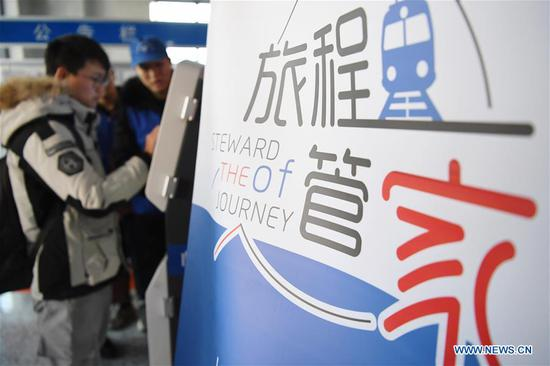 Volunteers help a passenger print his interim identity card at Lanzhou Railway Station in Lanzhou, capital of northwest China's Gansu Province, Jan. 13, 2020. During the Spring Festival travel rush, Lanzhou Railway Station and Lanzhou West Railway Station roll out a special voluntary service named