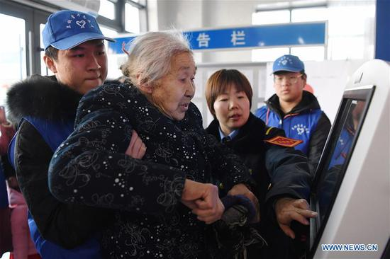 Volunteers help an elderly woman print her interim identity card at Lanzhou Railway Station in Lanzhou, capital of northwest China's Gansu Province, Jan. 13, 2020. During the Spring Festival travel rush, Lanzhou Railway Station and Lanzhou West Railway Station roll out a special voluntary service named