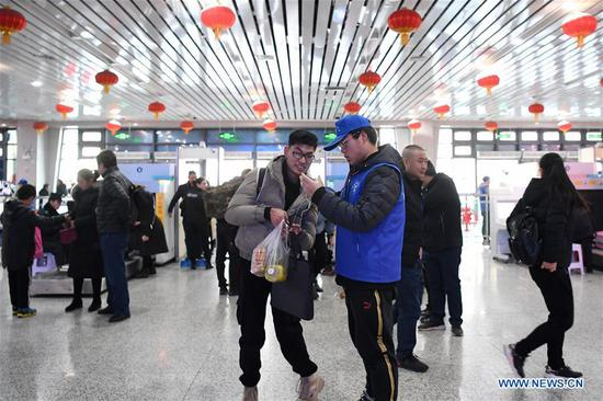 A volunteer provides service to a passenger at Lanzhou Railway Station in Lanzhou, capital of northwest China's Gansu Province, Jan. 13, 2020. During the Spring Festival travel rush, Lanzhou Railway Station and Lanzhou West Railway Station roll out a special voluntary service named