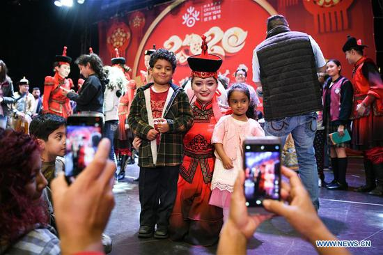 An actress from China's Inner Mongolia Autonomous Region pose for photos with audience at a celebration event greeting the upcoming Chinese Lunar New Year in Tlalnepantla, State of Mexico, Mexico, Jan. 17, 2020. (Xinhua/Xin Yuewei)