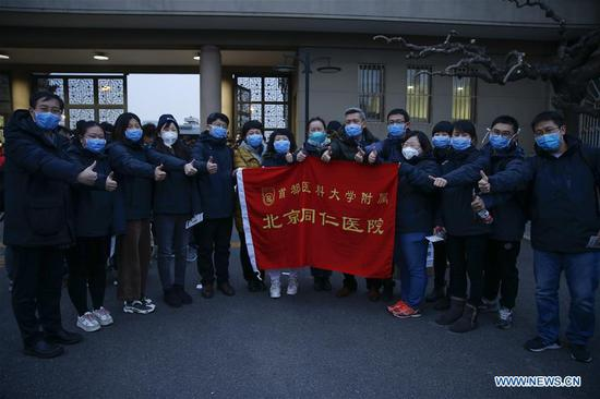Medical workers from Beijing Tongren Hospital pose for a group photo before leaving for Wuhan of Hubei Province, in Beijing, capital of China, Jan. 27, 2020. A team comprised of 136 medical workers from Beijing left for Wuhan City on Monday to aid the novel coronavirus control efforts there. (Xinhua/Zhang Yuwei)