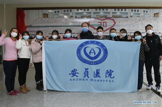 Medical workers from Anzhen Hospital pose for a group photo before leaving for Wuhan of Hubei Province, in Beijing, capital of China, Jan. 27, 2020. A team comprised of 136 medical workers from Beijing left for Wuhan City on Monday to aid the novel coronavirus control efforts there. (Xinhua/Zhang Yuwei)