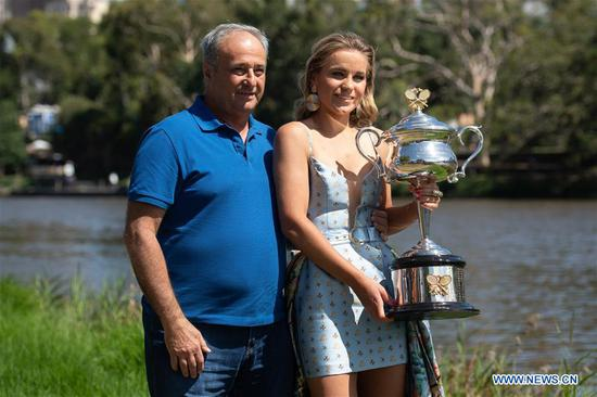 Australian Open women's singles champion Sofia Kenin (R) of the United States and her father Alexander Kenin pose for photographs with her trophy at Yarra River in Melbourne, Australia on Feb. 2, 2020. (Photo by Bai Xue/Xinhua)